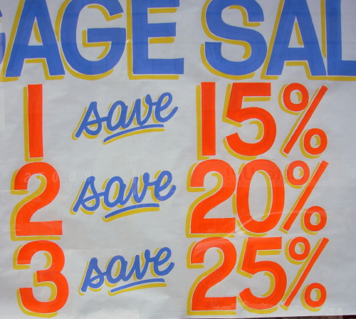Part of handwritten sign reads, with figures in orange, 1 save 15% 2 save 20% 3 save 25%