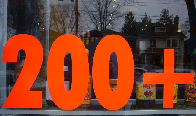 Vibrant orange type in a store window reads 200+
