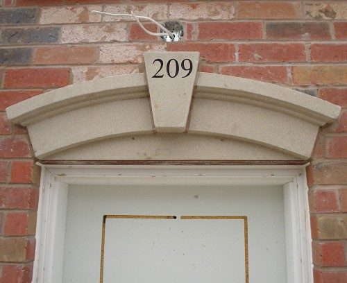 Photo shows concrete arch above unfinished door reading '209' in Times Roman. Wires protrude from an uncompleted light fixture above