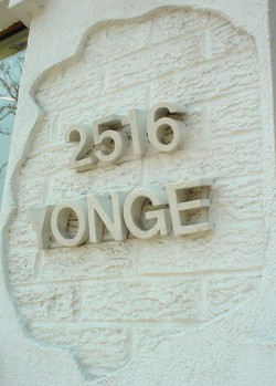 A hole cut in stucco surrounds the address '2516 Yonge' rendered in 3D letters that angle out of the brick wall