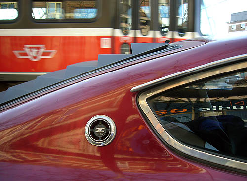Corner of burgundy car shows a Z logo in a circle behind angled rear window as a red streetcar whizzes by