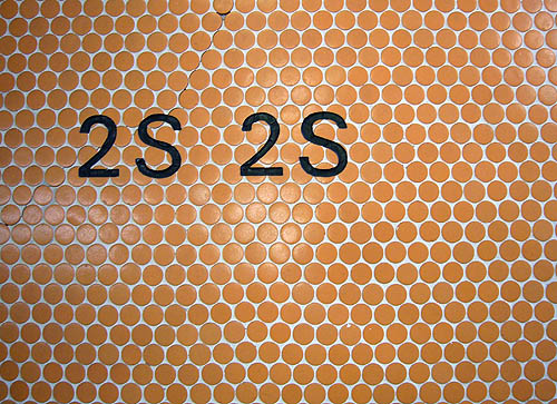 Type in Univers inscribed into a field of circular orange tiles reads 2S 2S