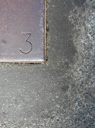 3 inscribed in steel plate installed on pavement
