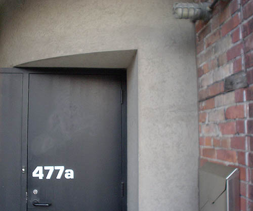 Flat black doorway, labelled 477a in Eurostile, sits nestled in quarter-cylinder of concrete alongside a brick wall