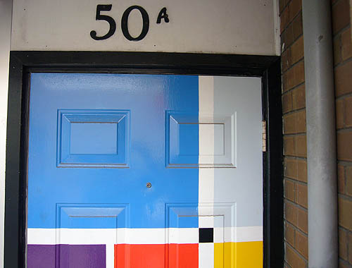 50A in metal letters sits above a door with blue, grey, purple, yellow, red, and black rectangles in a Mondrianesque pattern