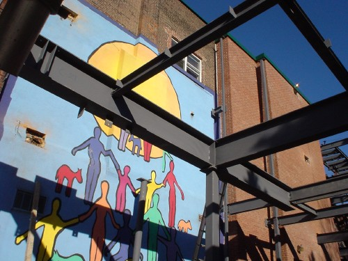 Black steel construction girders cast shadows on colourful mural of multicoloured human forms gaily holding hands