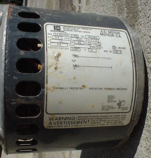 Round metal object is labeled A.C. MOTEUR MOTEUR C.A. with specifications and warning