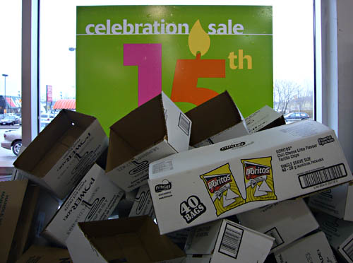 Sign in window reads celebration sale 15th and is obscured by a pile of empty boxes