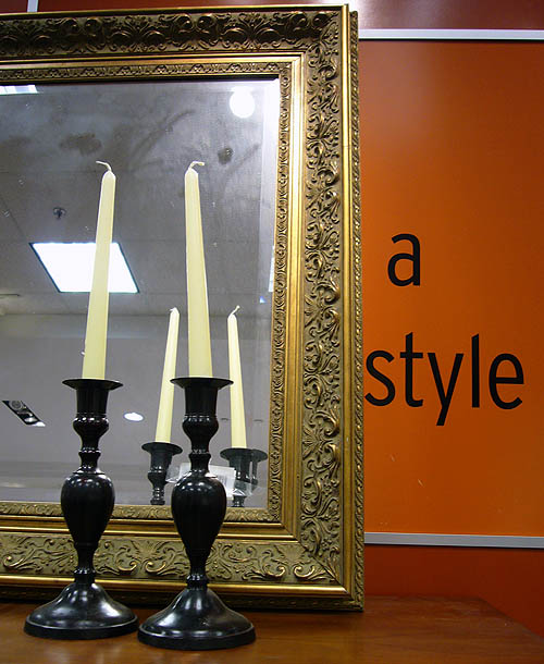 Two candles sit before  a fold-framed mirror that covers a wall, leaving the words 'a style' visible