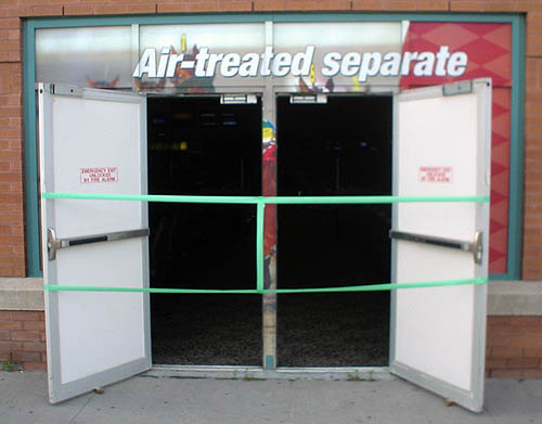 Opened doors, blocked off with green tape, lead to a dark interior and sit under a sign reading Air-treated separate