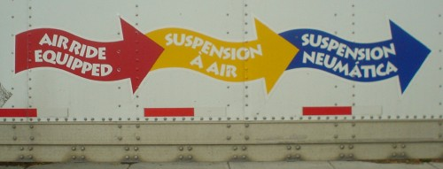 Logos on riveted steel panels read AIR RIDE EQUIPPED in a wavy red arrow, SUSPENSION À L'AIR in a yellow one, and SUSPENSION NEUMÁTICA in a blue one