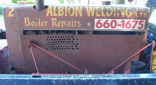 Rusted tank in pickup bed reads ALBION WELDING CO. LTD. Boiler Repairs in hand-drawn type. A phone number in Futura is displayed on a vinyl panel