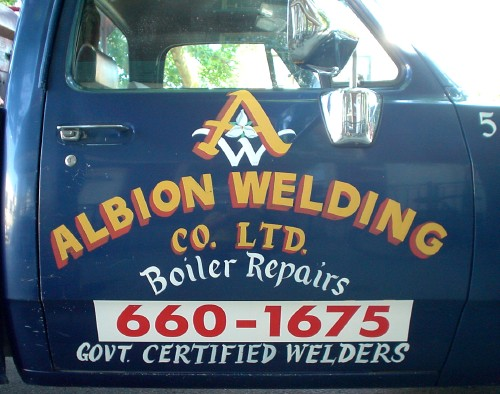 Door of pickup reads ALBION WELDING CO. LTD. Boiler Repairs in hand-drawn letters. A phone number in Futura is displayed on a vinyl panel