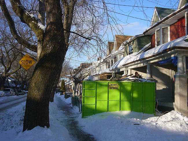 Bright green dumpster on wintry street