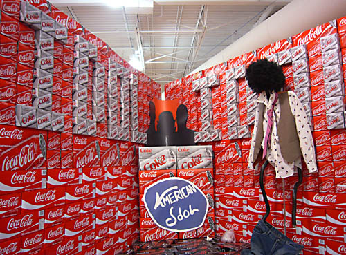 Giant display of Coke cases spells out IDOL on both walls, has a makeshift 'American Idol' logotype, and has a hanged effigy with its pants down