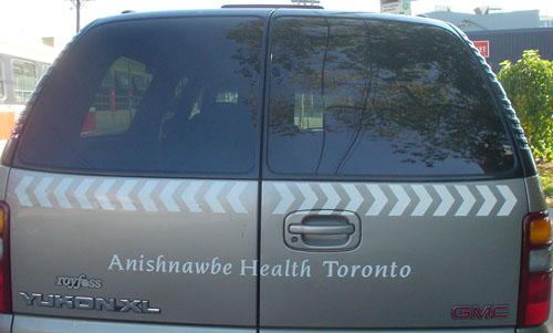 Dual ambulance doors of Suburban read Anishnawbe Health Toronto in Novarese Italic