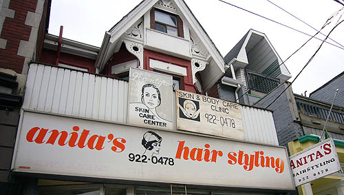 Sign reads anita's hair styling in orange italics, with other signs tacked above and extending from the end