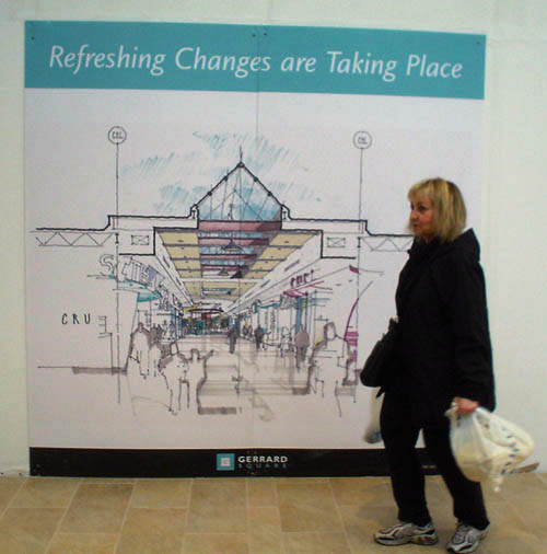 Blond-haired woman in sneakers and black jacket and pants carries shopping bags past large colour drawing of mall atrium labelled Refreshing Changes are Taking Place