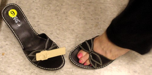 Woman's foot with pink nail polish tries on black sandal with patterned leather bow (right sandal still has security tag)