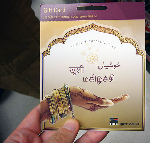 A finger behind a gift card with inscriptions in Urdu, Hindi, and Tamil appears to be connected to a photo of an upturned hennaed hand with bracelets