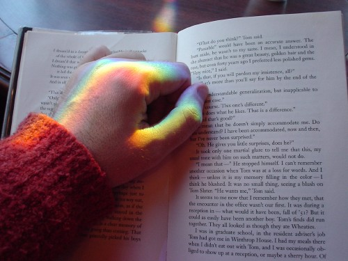 Rainbow hues refract on closed hand resting on an open book