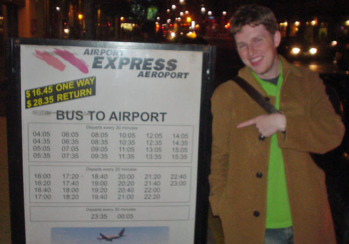 Matt Müllenweg, in green shirt and brown jacket, points jauntily at a sign for AIRPORT EXPRESS AÉROPORT giving BUS TO AIRPORT times in Arial