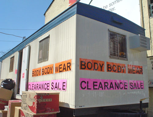 Trailer sits behind piled-up boxes and is emblazoned BODY BODY	 wEAR CLEARANCE SALE in Arial letters printed on orange, yellow, and pink sheets