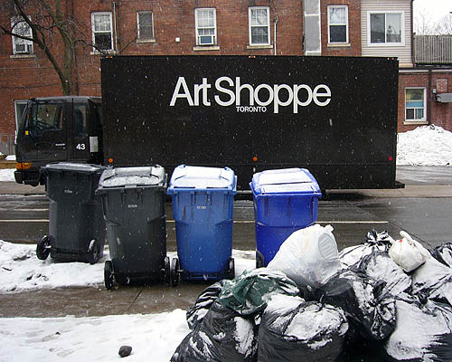 Art Shoppe delivery van sits parked across the street from two lines of snowy garbage bags and recycling bins