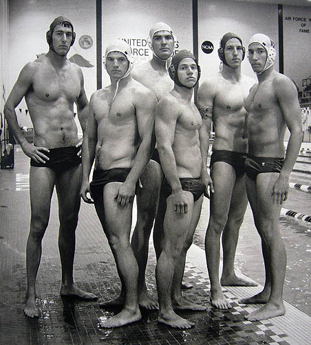 Black-and-white photo of five men in black swimsuits and water-polo helmets
