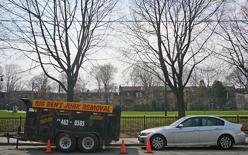 Trailer labelled BIG BEN'S JUNK REMOVAL sits parked at curbside in front of a BMW 3-series sedan