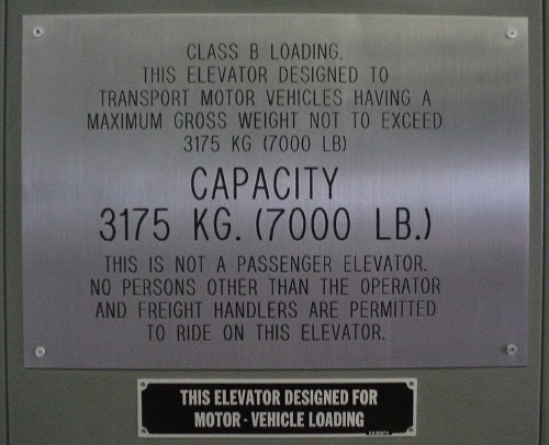 Stainless-steel warning sign affixed to elevator ('Class B Loading. This elevator desgined to transport motor vehicles.... This is not a passenger elevator')