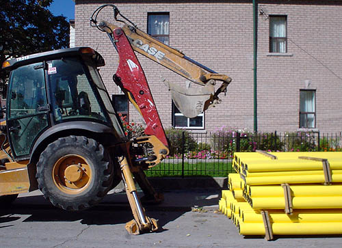Backhoe, jacked up on support legs, sits parked in front of bright yellow tubes in bundles stacked three high