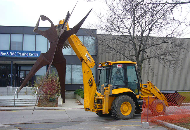 Backhoe carries rusted metal sculpture of a human form outside Fire & EMS Training Centre