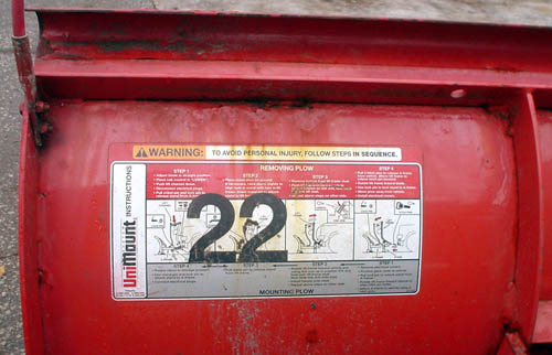 Illustrated warning label on back of bright-red snowplow blade has the number 22 in large Helvetica type