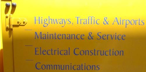 Yellow van door shows legends like 'Highways, Traffic & Airports' in blue Baker Signet type