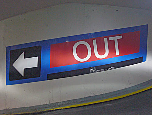 A red, black, and blue sign wrapped diagonally downward around a concrete column shows white Helvetica letters reading OUT