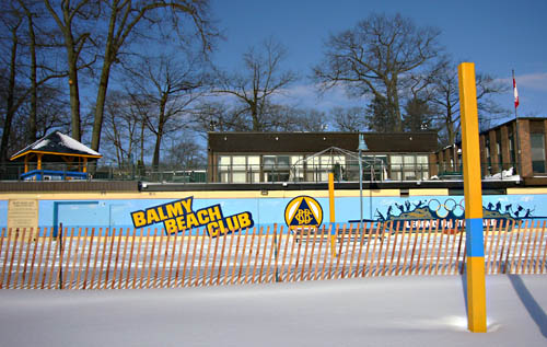 Wall emblazoned BALMY BEACH CLUB sits behind snow-covered ground and a snow fence