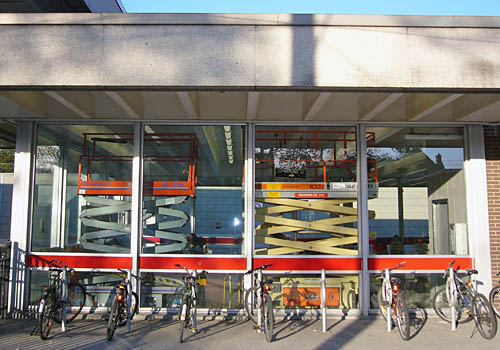 Behind a row of parked bicycles, one grey and one yellow scissorlift sit inside a subway station