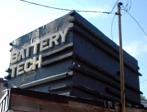 A dark-blue block the size of a small car sits atop a building. Its raised black ridges on two sides partially surround the words BATTERY TECH written in cutout white letters