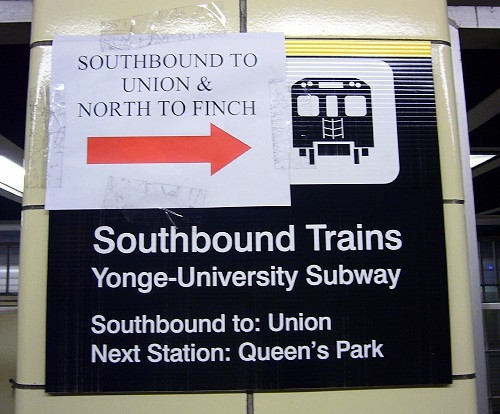 Printed sign says Southbound Trains Yonge-University Subway, with a laser-printed sign with a huge red arrow taped onto it reading SOUTHBOUND TO UNION & NORTH TO FINCH