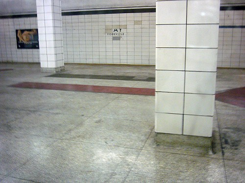 Filthy, decrepit, white-tiled subway station labelled AY YORKVILLE on far wall