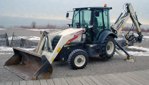 Front-end loader, raised up on its rear stabilizer feet, sits on beach sand behind boardwalk