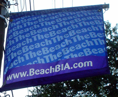 Blue banner reads TheBeach continuously in diagonal type across the main face and www.BeachBIA.com at bottom