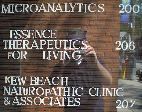Photo shows reflection of me (in purple-and-black hat) photographing a pegboard building directory with mismatched letters: ESSENCE THERAPEUTICS FOR LIVING 206