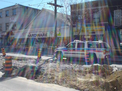 Lens flare streaks across photo of a Suburban labeled EMERGENCY TASK FORCE as it drives past a road's dug-up centre lane