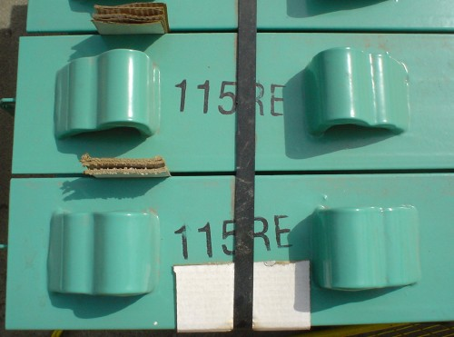 Teal-green railroad ties, labeled 115RE, are bound together and separated by cardboard wedges