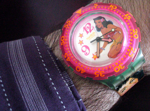Watch has bright pink outside dial and, on its face, an image of a woman in a bathing suit with a flower in her hair