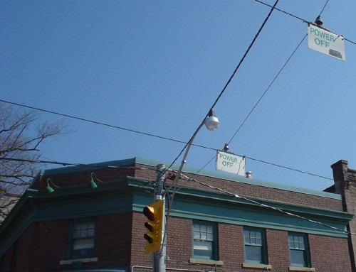 Signs hanging from overhead wires read POWER OFF against a blue sky