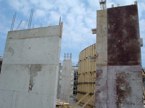 Construction site features tall flat concrete columns with rebar poking out from the tops and a curved wall made of wooden studs