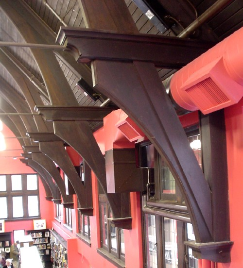 Giant dark wood brackets support a wooden vaulted ceiling against a red-painted wall